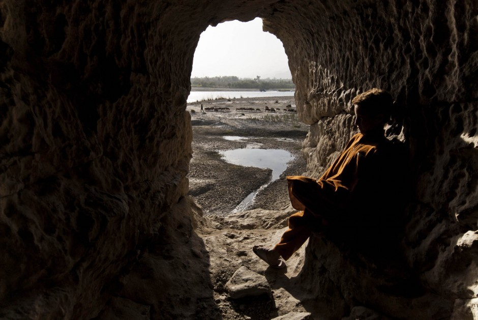 A boy enjoys a swatch of sunlight and the view of the Kabul River from a  cave once used for Buddhist meditation in Jalalabad. The Kabul and  Kunar rivers make Nangarhar province an agricultural center. All photos  by Daniel C. Britt.
