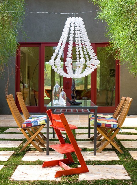 A fun and funky outdoor dining area features an unusual bubble chandelier (via KuDa Photography)