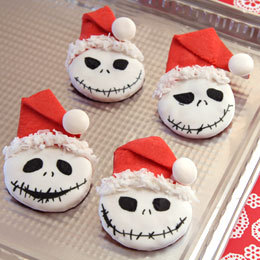 "Jack Skellington's Sandy Claws Cookies  Being the patron saint of Christmas is no small order. Just ask a  certain Pumpkin King (aka Sandy Claws) who once tried the jolly old  elf's hat on for size. While Jack is now apt to leave official holiday  business to the real Santa, he's still game to take part in a cookie  swap or two. You'll need: Batch of sugar cookie dough * Red food coloring  Disposable food preparation gloves (for kneading food coloring into the dough) Flour Wax paper Rolling pin Round cookie cutter (2.25-inch or so in diameter) Kitchen knife Spatula Baking sheet Wire cooling rack White cookie icing (the type that hardens when it sets) Flaked coconut Round white candies (such as Mentos) Black edible food marker Mini chocolate chips for grins Small green candies for buttons (such as M&Ms or jelly beans) Cocoa candy melts Ramekin or other small microwavable container to heat the candy melts Small chocolate candies for ears (such as Junior Mints) Red fruit snack (such as Fruit by the Foot) Kitchen scissors * Note: Homemade sugar cookie recipes tend to work best for these cookies. If you don't already have a favorite, try a Classic Sugar Cookie Dough recipe that's especially tasty and reliable.If  you choose one of the ready-made refrigerated doughs sold at grocery  stores, keep in mind that they tend to spread. You may want to knead in  additional flour to stiffen it and then bake a single cookie to see how  the dough holds up. If it still loses shape, try kneading in a bit more  flour and then chilling the cookies before you bake them. Instructions: 1. Divide the cookie dough into two equal portions. Knead red food coloring into one portion and leave the other one plain. 2. Working on a flour-dusted sheet of wax paper, roll out the plain  dough 1/4 inch thick. Use the round cookie cutter to cut out a bunch of  Jack Skellington face shapes. 3. Now roll out the red dough as  you did the plain. Using a kitchen knife, cut out a red triangular hat  shape (about 4 inches tall and 2 inches across the base) for each face.  Use the cookie cutter to cut a curved notch in the base of each hat, as  shown.  4. Top each of the faces with a  hat, draping the curved edge of the triangle over the top edge of the  circle. Use your fingertips to gently press down on the overlapped dough  layers (just enough to make them stick together). Then carefully fold  over the top of the hat, as shown.  5. Use a spatula to transfer the assembled cookies to a baking sheet,  and bake them according to the recipe directions. Allow the baked  cookies to cool briefly on the baking sheet before transferring them to a  wire rack to cool completely. 6. Spread white cookie icing on the face portion of each cookie. Then  set the cookies aside for a few hours to let the icing harden. 7. Use the edible marker to draw Jack Skellington facial features on  the hardened icing. For the best results, position the mouth close to  the lower edge of the cookie and leave a little space above the eyes to  trim the hat. 8. Now give each hat a ""fleecy"" brim by applying a line of cookie  icing along the edge and pressing coconut flakes into the frosting.  Lastly, stick a round white candy pompom to the tip of each hat. Once  the trim icing hardens, the cookies are ready to serve."