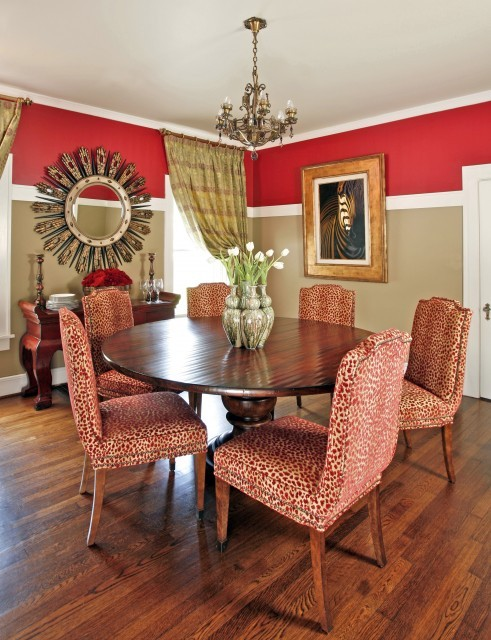 The dining room of this historic Texas home is enlivened with red and tan paint, and red cheetah print upholstered chairs pair nicely with antique furnishings. (via Dona Rosene Interiors)