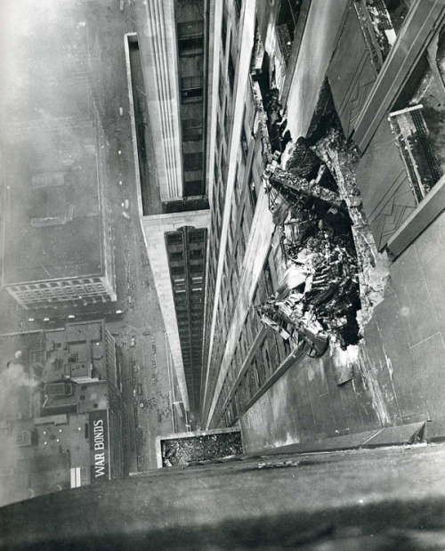 A B-25 bomber crashes into the Empire State Building on the morning of July 28, 1945. New York Times photographer Ernie Sisto had two of his friends hold his belt while he dangled off the side of the building to snap this photo.