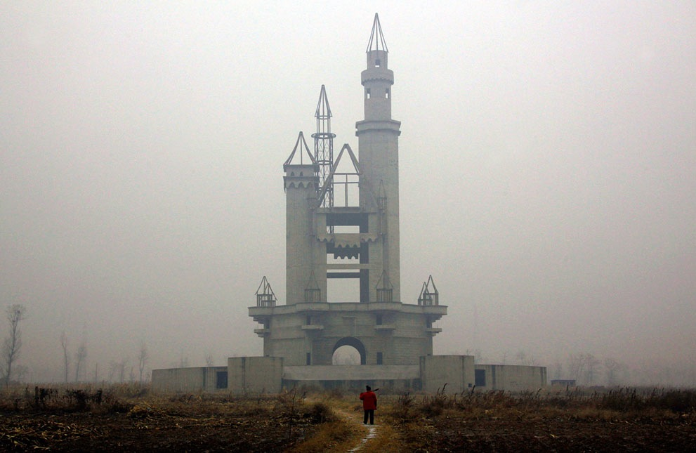 "Bag's Take-Away:   What's terrifying about that abandoned China theme park photo is the way it references the entrance to the Magic Kingdom, playing on the all-too-present fear that Recession America, formerly Frontierland, got lost in Fantasyland and has no Tomorrowland.   Full Slideshow at The Atlantic.  (photo: David Gray/Reuters caption: A farmer carries a shovel over his shoulder as he walks to tend his crops in a field that includes an abandoned castle-like building that was to be part of an amusement park called ""Wonderland"", on the outskirts of Beijing, China, on December 5, 2011.)   ————— Topping LIFE.com's 2011 list of Best Photo Blogs, follow us at: BagNewsNotes; BAG Twitter; BAG Facebook; Bag by Email."