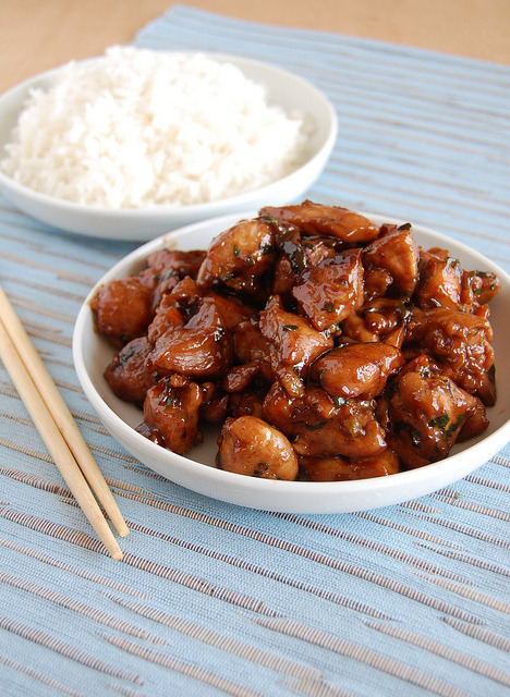 projecttastytreats:  Chicken Teriyaki slightly adapted from the wonderful Nigella Kitchen 2 tablespoons sake ¼ cup mirin (sweet Japanese Rice wine) ¼ cup soy sauce 2 tablespoons light brown sugar 2 teaspoons grated fresh ginger 4 spring onions, white part only, sliced splash of sesame oil 800g (1¾ pounds) chicken thigh fillets (no skin or bones), cut into bite-sized pieces ½ tablespoon neutral vegetable oil freshly ground black pepper handful of parsley leaves, chopped rice, to serve In a bowl large enough to hold all the chicken pieces, mix together the sake, mirin, soy sauce, sugar, ginger, spring onions and sesame oil. Add the chicken pieces and turn to coat each one of them in the sauce. Leave for 15-20 minutes. Heat the oil in a large, shallow frying pan (with a lid) and, using a perforated spoon, transfer the chicken pieces to the pan and sauté until they look cooked on the outside. Pour the marinade over the chicken, bring to a boil, then cover and turn down the heat, cooking for 5-10 minutes or until chicken is cooked through and sauce is thick. Stir in with freshly ground black pepper and the parsley. Serve immediately with rice. Serves 4-6