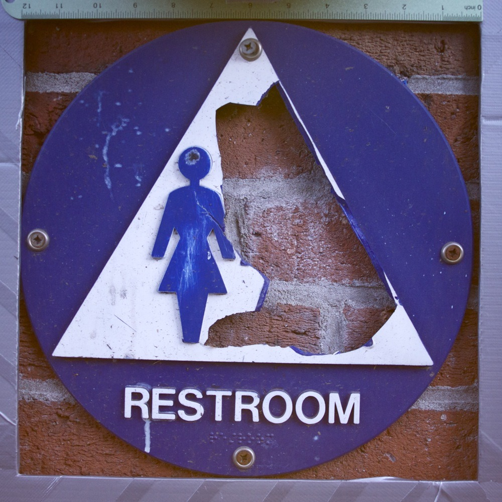 Blue and white unisex restroom sign with male figure broken off, public restroom at W Burnside and SW 8th.