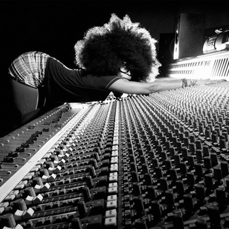 [Description: Black and white photo of Erykah Badu at a mixing board.]