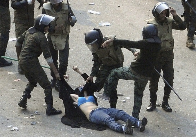This image, from the Reuters news agency, shows Egyptian army soldiers arresting a female protester during clashes at Tahrir Square in Cairo on Saturday. Soldiers beat demonstrators with batons in a second day of clashes that have killed nine people and wounded more than 300.