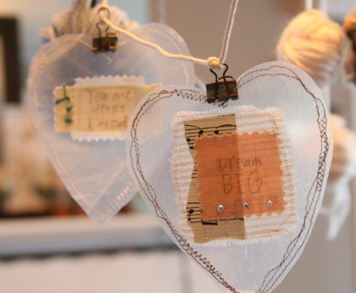 DIY Hanging Hearts Ornaments or for Valentine's Day. These are made out of cereal bags with notes inside and machine stitched - I like the delicate transparency that can't be achieved with fabric without a stiffiner. From personal experience frayed ribbon, some silver sequins, old fashioned script etc… looks best. You could even line the entire heart/whatever shape you want with different paper. Tutorial from crescendoh here.