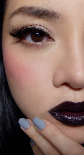 "Gothic Romance Tutorial: Black-Purple Lipstick with Winged Eyeliner (Inspired by Jordan Liberty) —- Pic above: Black liner, hot pink cheeks, and Noir lips, with slate grey nails Is ""wearable Goth"" makeup an oxymoron?  Not exactly.  This is not really a Goth look in the modern sense of the word, but rather, pulls from the late-medieval Gothic age, with its strange blend of opulence and dark dramatism. It's not always about matching over-the-top black lips and eyes.  Sometimes, beauty is as much what you do, as what you choose not to do. This look is a recreation of a Jordan Liberty look, and actually follows the very classic, feminine, 50s tenets. The eyes are extremely clean and more reminiscent of a 50s kitten eye than anything overtly ""Goth"", and the only touch of drama comes from the flicked liner and long flared lashes. The lips are the only thing that is slightly edgy about the look, blending black with a dark metallic purple for a 3D lip. To pull everything back so you don't look like a reanimated corpse, throw in an intense pink flush on the cheeks for a doll-like twist. —- Step 1: Apply a matte beige to the lids, and a slightly warmer medium toned apricot (both from the Wet n Wild Greed Palette) to the outer halves of the socket line for very subtle definition. As we want the look to be very clean, the eye lids should not be discolored.  —- Step 2: With a flat liner brush, apply black gel liner (Maybelline Lasting Drama) to the lids. As always, draw in the flick first, then the lash line. This allows you to really control the length and angle better.   The finished liner should give your eyes a slightly exotic tilt but not be so thick or angled upwards that you look like you're channeling a Sophia Loren look.  —- Step 3: False lashes. I applied very full synthetic lashes (Fairy Lash #10 from Sasa), longer at the outer corners than the inner. The longer outer edges will lift your eyes upward. (Try something like Red Cherry 043s for a similar shape, although these are not as full.)  The curve of your lashes should more or less follow the curve of your liner earlier.  —- Step 4: Apply a hot pink blush (NYX Pinky) high on the cheeks. Pull it in further towards the center of your face than you would normally wear, just to give it a bit more of a doll-like look. And I hate to say this, but you CAN go a bit heavier than usual, as it needs to balance out the strong black lips.  —- Step 5: This is the scary part. Use a black liner to rim the edges of your lips. If you have small lips like me, leaving the center of the cupids bow bare so you don't close off your whole mouth.   —- Step 5: Fill in the outsides with black lipstick (L.A. Girl Creme Lipstick in Dreamer), and then run a dark metallic purple (Make Up Store Magic lipstick) in the center of the lips and blend outward slightly. If you can't find a dark purple metallic lipstick, the EASY way to do this is to dab MAC Grape pigment around the center of your lips and then press them together to distribute. Then apply a tiny touch of Vaseline or Rosebud Salve to return some shine without making the lip look glossy.  —- You can always choose to go all-black on the lips, as long as you keep the overall texture creamy, not matte. The look you're going for is enigmatic, but still pretty and soft. (Well, as soft as a look can be with black lipstick anyway.)  —- On the Nails: Revlon Top Speed Nail Enamel in 810 Hazy"