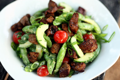 foodsmyaddiction:    Asian Sugar Snap Pea ans Steak Salad [Recipe] Ingredient: 3 cups fresh sugar snap peas, blanched & chilled 2 tablespoons soy sauce 1 tablespoon hoisin sauce 1 tablespoon minced peeled fresh ginger 2 cloves fresh garlic, minced  1 tablespoon canola mayonnaise 1 tablespoon peanut butter 2 teaspoons rice wine vinegar 1 teaspoon dark sesame oil 1 pint cherry tomatoes, halved 1 1/2 cups chopped seeded English cucumber (about 1) 4 green onions, chopped 1 tablespoon olive oil 8 ounces flank steak, cut into small pieces 1/4 teaspoon kosher salt 1/4 teaspoon freshly ground black pepper 2 tablespoons toasted sesame seeds, optional Directions: To blanch peas: Bring a pan of water to a rolling boil. Place peas in boiling water for one minute. Remove with a slotted spoon to a bowl of ice water.  Drain the peas when they are completely cold; set aside. In a medium bowl, combine soy sauce and next 8 ingredients (through sesame oil), stirring with a whisk. Add sugar snap peas, tomatoes, cucumber, and onions; toss to coat. Right before serving, heat a medium cast-iron skillet over high heat. Add olive oil to pan; swirl to coat. Combine steak, salt, and pepper, tossing to coat steak. Add steak mixture to pan; cook 5 minutes or until well browned and crisp, stirring frequently.  When ready to serve, Combine peas, cucumbers, tomatoes, and green onion and toss to combine.  Drizzle with dressing and toss until well coated.  Divide into 4 portions and top with steak.  4 Servings (serving size: 1 1/2 cups)Calories: 290 ▪ Fat: 16g ▪ Carbs: 15g ▪ Dietary Fiber: 4g ▪ Protein: 21g