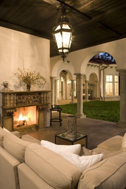A magnificent Mediterranean-style covered loggia with stone columns and fireplace. (via John Kraemer & Sons)