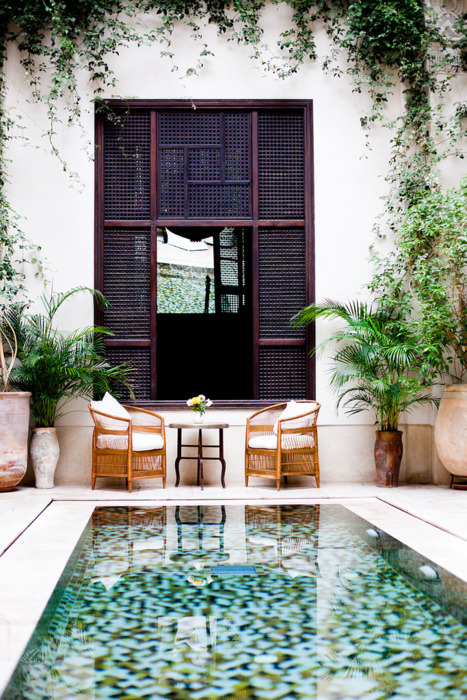 A tiled pool and wooden-screened windows give this patio an exotic feel