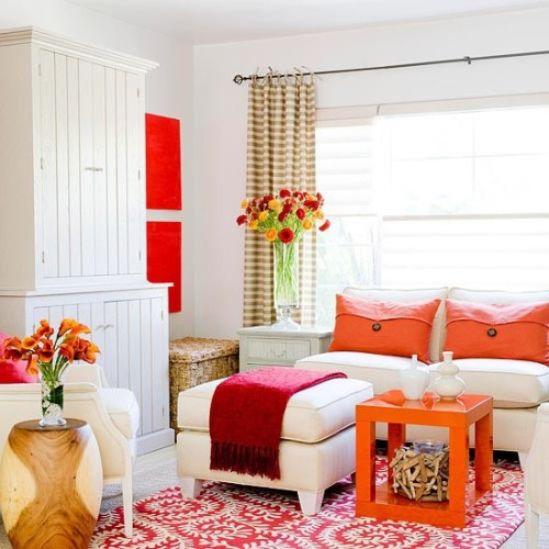 Bold splashes of orange and red give this all-white room a new look with little effort.  An orange table with modern lines adds a sassy touch to the decor. (via Living and Dining Spaces)