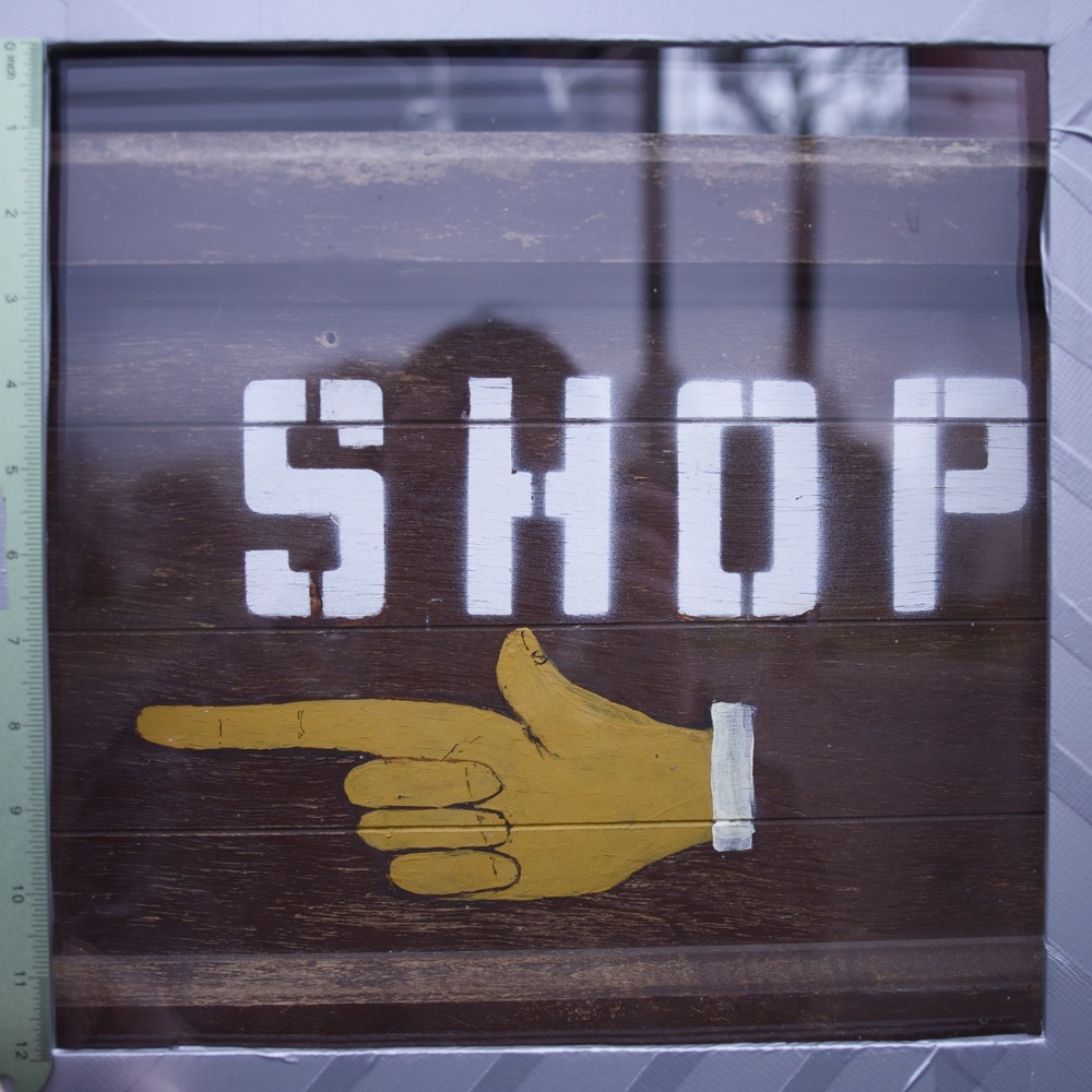 "Sign in storefront, ""SHOP"" and pointing index finger symbol, N Lombard St. This is the window of a barbershop that I am not sure I have ever seen open in the last three years."