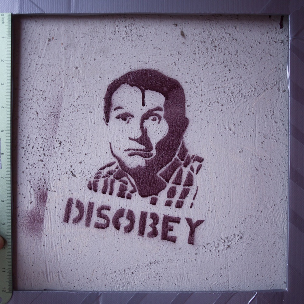"Maroon spray paint stencil graffiti riffing on Shepard Fairey, Ed O'Neill (presumably as Ed Bundy from Married With Children) over ""DISOBEY"", N Lombard St. There was also a graffiti of Ron Jeremy nearby with a QR code speech bubble sticker next to it, but I thought this one was more interesting."