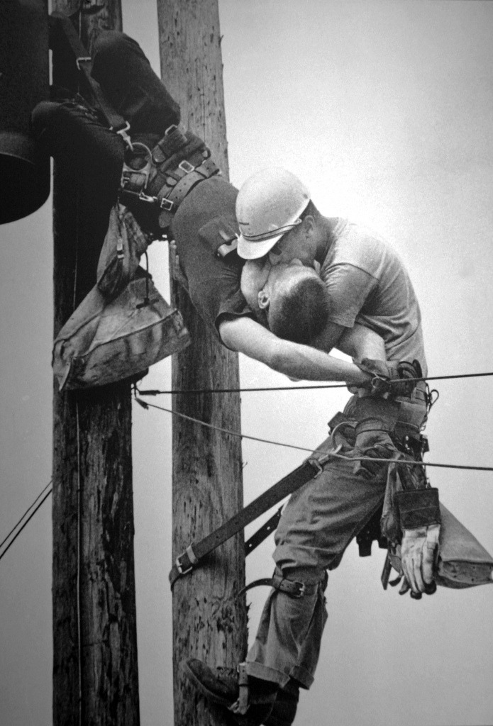 "The Kiss Of Life by Rocco Morabito, 1968 Pulitzer Prize.   Jacksonville Journal photographer Rocco Morabito is on his way to photograph a railroad strike when he notices Jacksonville Electric Authority linemen high up on the poles. ""I passed these men working and went on to my assignment,"" says Morabito. ""I took eight pictures at the strike. I thought I'd go back and see if I could rind another picture."" But when Morabito gets back to the linemen, ""I heard screaming. I looked up and I saw this man hanging down. Oh my God. I didn't know what to do."" The linemen. Randall Champion, is dangling upside down in his safety belt — felled bv 4,160 volts of electricity. ""I took a picture right quick."" says Morabito. ""J.D. Thompson (another lineman) was running toward the pole. I went to my car and called an ambulance. I got back to the pole and J.D. was breathing into Champion."" Cradling the stricken lineman in his arms, Thompson rhythmically pushes air into Champion's lungs. Below. Morabito makes pictures — and prays. ""I backed off. way off until I hit a house and I couldn't go any farther. I took another picture"", it is a prize-winning photograph, but Morahito's real concern is the injured lineman. Thompson finally shouts down: ""He's breathing."" Champion survives."