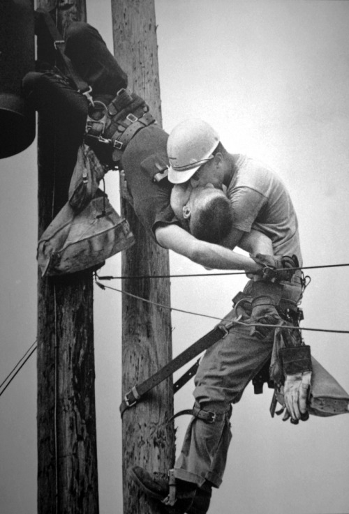 "silfarione:  The Kiss Of Life by Rocco Morabito, 1968 Pulitzer Prize. Jacksonville Journal photographer Rocco Morabito is on his way to photograph a railroad strike when he notices Jacksonville Electric Authority linemen high up on the poles. ""I passed these men working and went on to my assignment,"" says Morabito. ""I took eight pictures at the strike. I thought I'd go back and see if I could rind another picture."" But when Morabito gets back to the linemen, ""I heard screaming. I looked up and I saw this man hanging down. Oh my God. I didn't know what to do."" The linemen. Randall Champion, is dangling upside down in his safety belt — felled bv 4,160 volts of electricity. ""I took a picture right quick."" says Morabito. ""J.D. Thompson (another lineman) was running toward the pole. I went to my car and called an ambulance. I got back to the pole and J.D. was breathing into Champion."" Cradling the stricken lineman in his arms, Thompson rhythmically pushes air into Champion's lungs. Below. Morabito makes pictures — and prays. ""I backed off. way off until I hit a house and I couldn't go any farther. I took another picture"", it is a prize-winning photograph, but Morahito's real concern is the injured lineman. Thompson finally shouts down: ""He's breathing."" Champion survives."