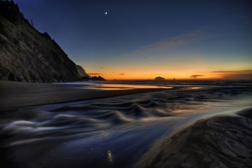 Tides Near Port Orford, Oregon by Randy Sholten About the photo:  The photo above shows Brush Creek rushing across a wide beach at low tide near Port Orford, Oregon. It was snapped at the base of Humbug Mountain a little past sunset on November 28, 2011. Venus and the waxing crescent Moon are conspicuous in the twilight sky.