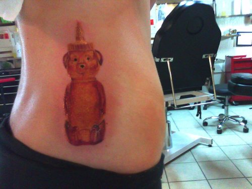 This is my honey bear tattoo. It's on my lower back/hip area and this picture was taken only minutes after it was done. I got this because my mother owns two breakfast restaurants and when I was little I would always take the honey bears off all the tables and play with them. I always got scolded for squirting the honey right into my mouth. This is just to represent my mother and my childhood. It has got to be one of my favorite tattoos and I fall in love with it more and more every day.  It was done by Vince LeBlanc at Royal Flesh Tattoo in Chicago.