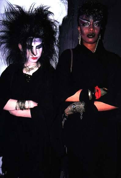 gorgonetta:  [Color photo of a couple of tradgoths in very serious makeup and black clothing, standing with their arms folded.] They look pretty fierce.