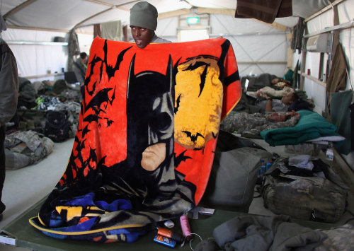 "Batman provides comfort in Kuwait. ""U.S. Army Specialist Robert Jackson from Washington, DC of the 2-82 Field Artillery, 3rd Brigade, 1st Cavalry Division, folds up his blanket for one last time as he prepares to pack his gear for the flight home after his unit exited from Iraq on December 14, 2011 at Camp Virginia, near Kuwait City, Kuwait. America's military continues its pullout of Iraq which is scheduled to be by the end of this year, after eight years of war and the overthrow of Saddam Hussein. (Photo by Joe Raedle/Getty Images)"""