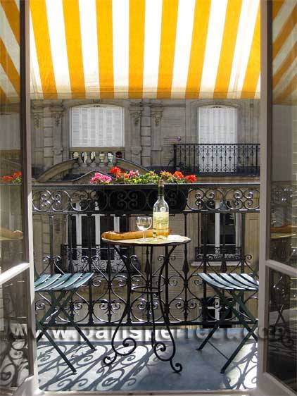 A cute, typically Parisian iron apartment balcony, with a brightly colored striped awning and romantic seating for two. Naturally, being in Paris, the table is laid with wine and a crusty baguette. :) (via the paris apartment)