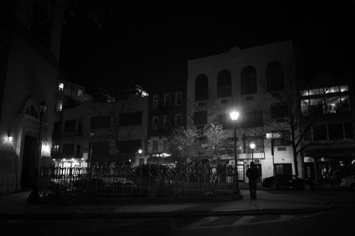 "Night. East Village, New York City.  As the city moves furtively into shadows, buildings render themselves one by one in the cold glow of street lamps whose light burns brightly against the dark expanse of night: supernovas pushing against gravity and their inevitable collapse into themselves.  And we wait: unaware of the solemnity of the situation.   We wait under these man-made white dwarfs pushing our dreams to the skies beyond our grasps forever propelling ourselves forward while standing completely still.    —-  View this photo larger and on black on my Google Plus page  —-  Buy ""Gravitational collapse - Night - East Village - New York City"" Posters and Prints here, View my store, email me, or ask for help."