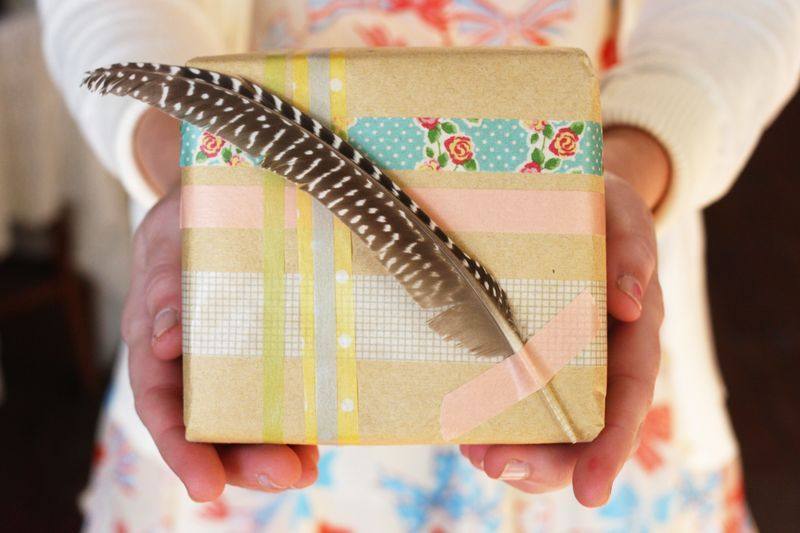 It's time to cram in the gift wrapping. Here are 2  simple gift wrap ideas from A Beautiful Mess! 1. The first uses japanese washi tape!. Just layer the  washi tape in a plaid inspired pattern and tape a spotted feather on to  finish the look!    2. Wrap your gift in atlas paper. You can thrift an atlas book, then add a piece  of yarn, a silver pipe cleaner heart and a white feather to top it  off!  For more ideas, check out Elsie's Blog!