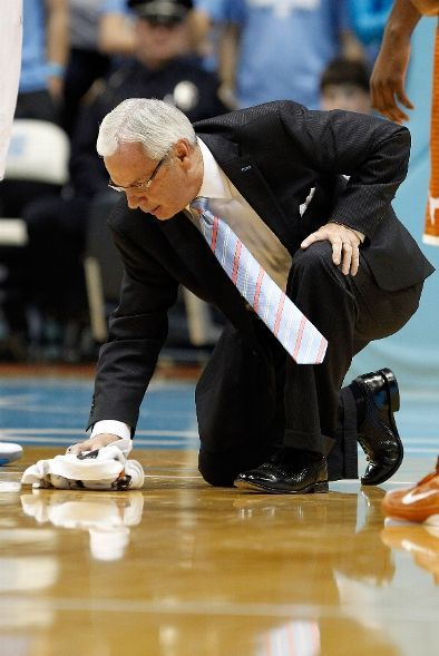 uncbball:  Head coach Roy Williams of the North Carolina Tar Heels wipes off the floor during their game against the Texas Longhorns