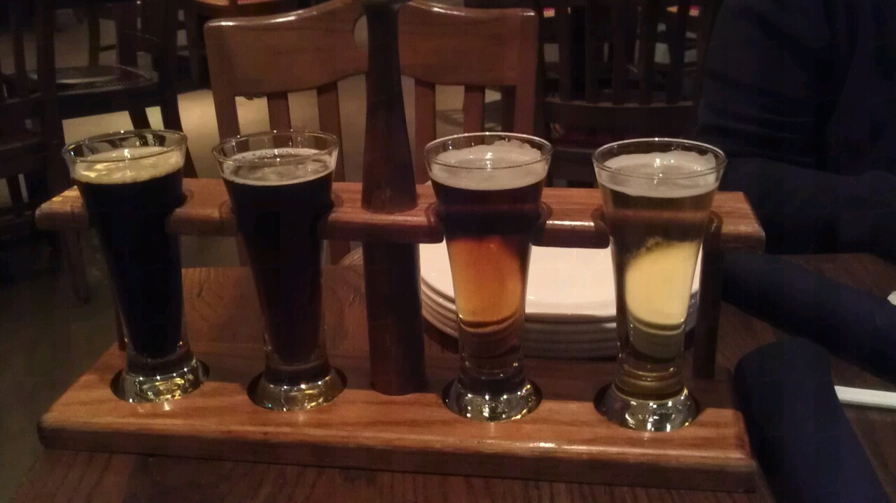 Tasting some beers for my birthday at the Mad Fox Brewing Co. in Falls Church. Thought I should try the local beer game while I was in town. I have a cold, but I don't care. Beer never rests. Left to Right: Stir About Oatmeal Stout, which was pretty run of the mill, not a lot going on, a little weak for my taste, needs more dark and toasty. Reynard Black Saison was the most interesting of the bunch. It was chocolaty but sour like a chocolate orange or something.  Altbier is a style I haven't tried as far as I know, but this wasn't a great introduction. It just tasted like a boring amber ale with a misplaced bitterness.  Kellerbier Kölsch is also strangely bitter. It tasted like the other kölschs I like, but left a bitter tannin or lemon peel taste. It was just off.