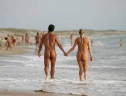 Family Naturism Couple holding hands at a nude beach