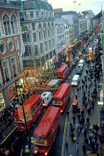 bewitchingbritain:     Oxford Street in London, England, at Christmastime. Oxford Street is not anywhere near the city of Oxford -which is about 60 miles/90 km north west of London- and is a major thoroughfare in the West End. Oxford Street is one of Europe's busiest shopping streets, with approximately 300 shops. I LOVE those little tiny people on the street shots and I have no idea why. Someone needs to psychoanalyse me. Then again, better not. (gettyimages.com)