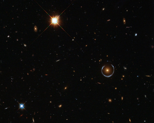 From Astronomy Picture Of The Day; December 21, 2011: A Horseshoe Einstein Ring from Hubble ESA/Hubble & NASA What's large and blue and can wrap itself around an entire galaxy? A gravitational lens mirage. Pictured above, the gravity of a luminous red galaxy (LRG) has gravitationally distorted the light from a much more distant blue galaxy. More typically, such light bending results in two discernible images of the distant galaxy, but here the lens alignment is so precise that the background galaxy is distorted into a horseshoe — a nearly complete ring. Since such a lensing effect was generally predicted in some detail by Albert Einstein over 70 years ago, rings like this are now known as Einstein Rings. Although LRG 3-757 was discovered in 2007 in data from the Sloan Digital Sky Survey (SDSS), the image shown above is a follow-up observation taken with the Hubble Space Telescope's Wide Field Camera 3. Strong gravitational lenses like LRG 3-757 are more than oddities — their multiple properties allow astronomers to determine the mass and dark matter content of the foreground galaxy lenses.