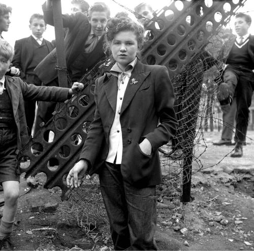 burnedshoes:  © Ken Russell, 1955, Teddy Girls 14-year-old Jean Rayner in the exploratory stage of Teddyism. The following images are from Ken Russell's January 1955 series 'The Last of the Teddy Girls'. Long before Ken Russell, who passed away in late November, became the notorious film director responsible for Women in Love, The Devils, The Boyfriend and The Who's rock opera Tommy, he was an art student and, later, a freelance photographer.In 1955, the fledgling photographer created a series called The Last of the Teddy Girls, which featured photographs taken against the war-torn backdrop of London's East End. The images are one of the first reportage series to be made of British youth culture, presenting pictures of working class girls in Neo-Edwardian dress—a fascinating counterpoint to their drape-coated and drainpipe-wearing male counterparts the Teddy Boy. The Last of the Teddy Girls also provided a rare and unique glimpse of a little recognized and under-documented subculture of austere post war Britain. (read more / see more photos)