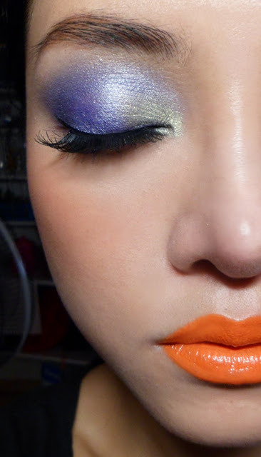 Lime Crimemy Beautiful Rocket: Orange lipstick and Indigo lidd tutorial —- What goes with a super-bright, true-orange lip?  Well warm Fall colors like russets and golds would look good, but you can also swing the other way and do contrasting shades in bright tones. To keep things soft, I am using shimmer instead of matte, which would be a bit stronger. Step 1: I'm using a shimmery dusty blue-purple (try Lime Crime Twilight) for the outer 2/3 of the lid.   Step 2: Using a soft golden green, I fill in the inner corners of the lid, blending just slightly into the blue. (The Body Shop #44 Single Eyeshadow)  Step 3: Line the upper lash line with a purple pencil (Bourjois Regard Effet Metallise #78 Bleu Chatoyant). Add a pale golden green pencil (Bourjois Contour Clubbing Liner #44 Golden Grey Session) to the lower lash line.   Step 4: Apply black liquid liner along the upper lash line and then add a pair of false lashes. (Any that are not too cat-like and flared at the outer corners will do.)  On the cheeks: NYX Cinnamon Blush -  a matte vermillion-orange (red-toned) On the lips:  Lime Crime My Beautiful Rocket - a bright true-orange lipstick