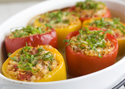 prettygirlfood:  Orzo-Stuffed Peppers Serves 4-6 1 (28-oz) can whole Italian tomatoes 1 tablespoon dried oregano 1/2 cup grated Parmesan 1/4 cup extra-virgin olive oil 3 garlic cloves, minced 1 teaspoon salt 1 teaspoon freshly ground black pepper 4 cups low-sodium chicken broth (or vegetable broth for a vegetarian dish) 1 cup orzo 6 sweet bell peppers (red or yellow) 1/4 cup chopped basil Preheat oven to 400 degrees.Pour the tomatoes and their juices into a large bowl and break them into pieces using kitchen shears or your fingers. Add the oregano, cheese, olive oil, garlic, salt and pepper. Stir to combine.Meanwhile, bring the chicken broth to a boil in a medium saucepan over high heat. Add the orzo and cook for 3 minutes. The orzo will be only partially cooked. Drain the orzo through a sieve, reserving the chicken broth. Add the orzo to the tomato mixture and stir to combine. Transfer the warm broth to a 3-quart baking dish.Slice the tops off the peppers and remove all the inner ribs and seeds. Cut a very thin slice from the base to help the peppers stand up.Spoon the orzo mixture into the peppers. Place the peppers in the baking dish with the warm chicken broth. Cover the dish with non-stick foil and bake for 45 minutes. Remove the foil, sprinkle each pepper with cheese, and continue baking until the cheese is golden, about 15 minutes. Remove from oven and carefully transfer the stuffed peppers to serving plates. Garnish with basil, if desired.
