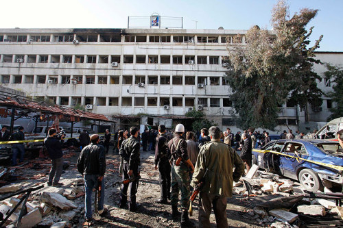 fotojournalismus:  People stand at the site of the suicide bombing, Damascus, Syria on December 23, 2011. Two massive explosions have rocked the centre of the Syrian capital, Damascus, killing at least 30 people and injuring 100. It was unclear who was responsible for the devastating car bombings, apparently set off by twin suicide bombers outside the offices of Syria's security and intelligence agencies. They came just hours after a delegation of observers from the Arab League arrived in the country. Guardian's Live Blog|Al Jazeera's Live Blog [Credit : Muzaffar Salman/AP]