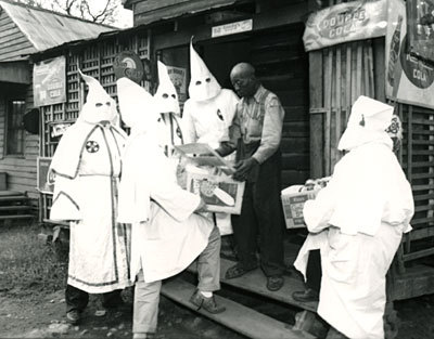 "Thomas Hamilton and other Klan leaders deliver a Christmas package to one of Augusta's African American citizens. (Robert J. Wilkinson Collection, Augusta Museum of History)   ""The klan, he said, obtained a large list of needy from the welfare department and then distributed the food baskets and money after a committee had determined what were considered the most worthy cases. The klan spokesman said the 'ladies organization' of the Augusta Klavern also has given food baskets valued at more than $150 in addition to those given by the men. The baskets, he added, were given 'indiscriminately' and went to both white and Negro families.  The audacity."