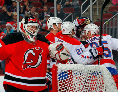 NEWARK, NJ - DECEMBER 23: Goalie Martin Brodeur #30 of the New Jersey Devils looks back as Jason Chimera #25 of the Washington Capitals celebrates with teammates after he scored his first of two goals during the third period of an NHL hockey game at Prudential Center on December 23, 2011 in Newark, New Jersey. Devils won 4-3 in a shootout. (Photo by Paul Bereswill/Getty Images)
