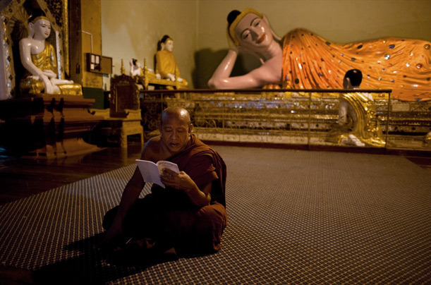 A monk studies in a shrine dedicated to the reclining Buddha at Shwedagon Pagoda, Burma. [Credit : James Nachtwey] [via]