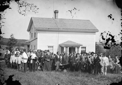 Andreas Larsen Dahl, Funeral Party around Casket. Deerfield, Wisconsin, ca. 1874. Source: Wisconsin Historical Society.  A funeral party is assembled around a casket in front of an upright-and-wing frame house. Two older men on the left, one identified as Lars D. Reque, stand with bibles while several women wearing Norwegian-style patterned shawls are standing close to the casket. This is another house insured by the Hekla Fire Insurance Co., which sold to many Norwegian-American households in south central Wisconsin.