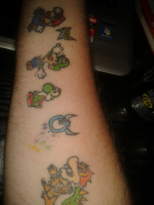 These were my first tattoos (I have the other arm done in a similar fashion). they represent my time at university so far (I'm in my 2nd year now) and especially the time I've spent with my housemates playing computer games and throwing obscenities at the television. These are some of the best times of my life so far. So this tattoo is for my housemates at University. I love them all so much.It was done by Missi Clare who now works at a tattoo palour in Ealing Broadway, London =).