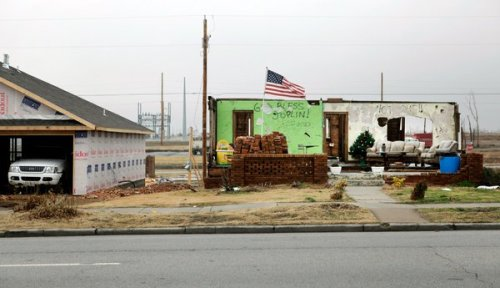 The remains of a home, belonging to Joplin, Missouri resident Tim  Bartow, remains standing in the town devastated by a tornado earlier  this year, when 161 of its residents died.  Officials are now trying to determine what to do with the structure, called the Volunteer House,  which is open to the elements and bears handwritten notes and mementos  from the legions of volunteers that came to help.  (Photo: Steve Hebert /  The New York Times)