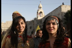 aljazeera:  Palestinian girls gather outside the Church of the Nativity, which is built over the site where Christians believe Mary gave birth to Jesus in a stable and then laid him in an animal's feeding trough, or manger [AFP]