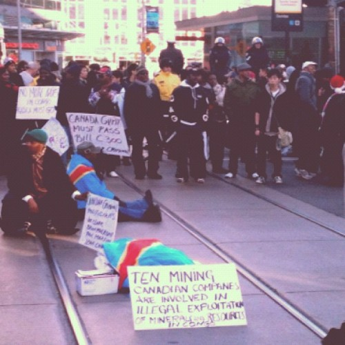 nelwyn:  Boxing day! #toronto #protest #congo  (Taken with Instagram at Yonge-Dundas Square)  Protestors in my hometown drape themselves in the oft-changed flag of the Democratic Republic of Congo.