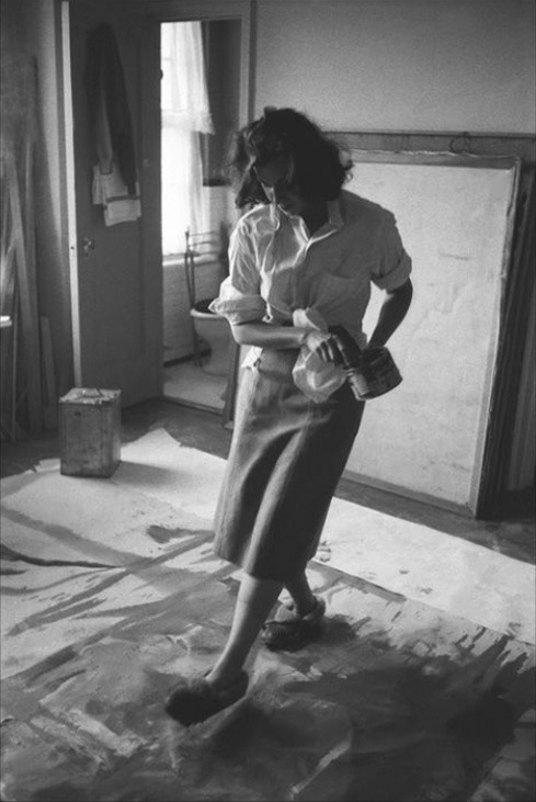 Helen Frankenthaler using slippers to distort paint applied to the canvas.