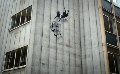 A new stencil and spray paint piece by graffiti artist Banksy appears on a vacant building in the Mayfair area of London. (The Daily Frame)