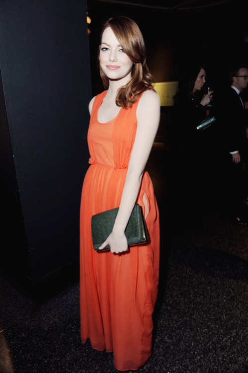 teenvogue:  Emma Stone wears a cheery winter look in a clementine Carven dress. A sleek clutch from The Row tops off the ensemble. Get the full fashion breakdown here »