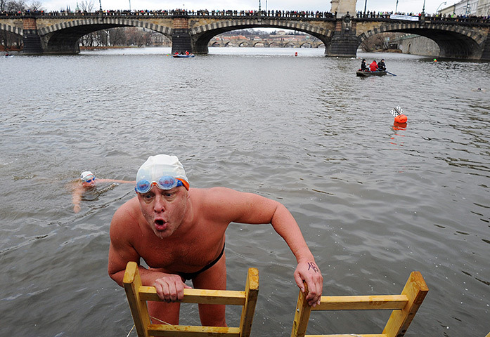 Prague, Czech Republic A swimmer reacts as he climbs out of the Vltava river after the traditional Christmas winter swimming competition (via guardian.co.uk)