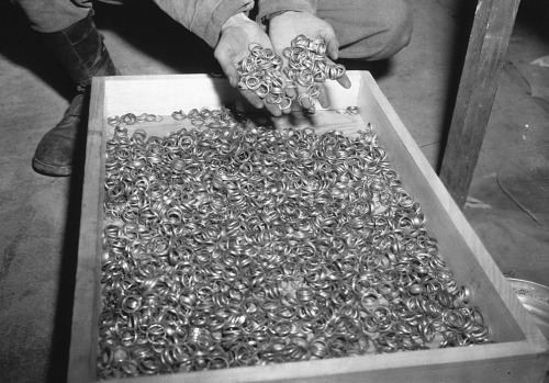 "picturesofwar:  ""A U.S. soldier inspects thousands of gold wedding bands taken from Jews by the Germans and stashed in the Heilbronn Salt Mines, on May 3, 1945 in Germany."" Source"