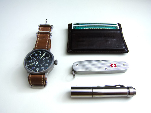 submitted by daniel  I have been refining my EDC and I think I nailed it. -The watch is a Laco type B with a Corvus Horween NATO strap.-SAK Cadet -I love how thin it is!-4Sevens Preon 1 - Carrying this is much easier than my HDS Clicky.-Coach card case  Editor's Note: Great minimalism here. The Cadet/Preon 1 pair is great. Those Alox Cadets are a great value, work well for many EDCers and carries so easily. I like the Preon 1 as it's one of the few 1xAAA lights with both a pocket clip and a click switch too. Lastly, beautiful LACO flieger too. Thanks for sharing!